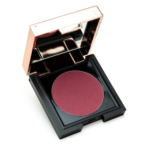 "A small black square compact with a rose gold lid containing a mirror sits open, revealing a circle of warm, rich plum powder Chic to Chic blush in ""Bashful."""