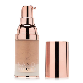 A frosted cylindrical bottle of Dazzle liquid shimmer with a rose gold gold pump, its rose gold cap sitting beside it on a white background. The color is Turned On, a gentle glitter of tan.