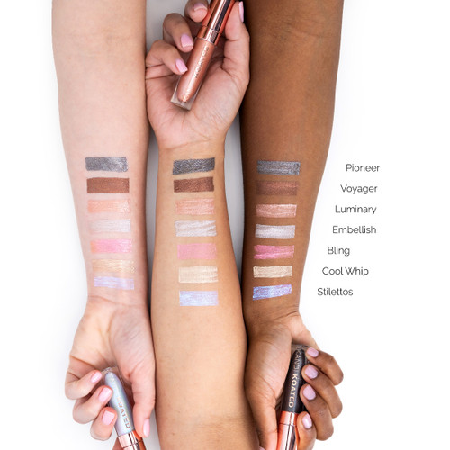 An image of three outstretched arms of differing skin tones showcasing different colors of Luster liquid metal eyeshadows in swatches on each arm for comparison. Each hand clasps a different tube.